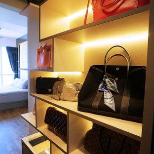 Ejemplo de armario vestidor de mujer, moderno, pequeño, con puertas de armario beige y suelo de madera oscura