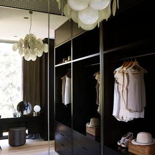 Foto di una piccola cabina armadio unisex contemporanea con ante lisce e ante in legno bruno