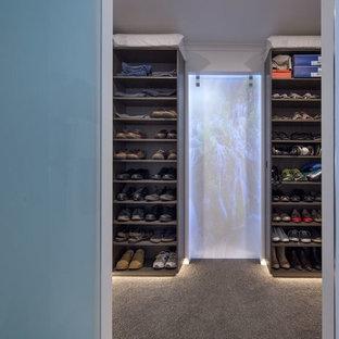 Modelo de vestidor unisex, minimalista, de tamaño medio, con armarios estilo shaker, puertas de armario de madera en tonos medios y moqueta