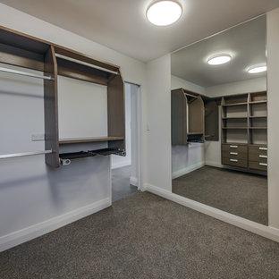Immagine di una cabina armadio unisex stile marinaro di medie dimensioni con nessun'anta, ante in legno bruno, moquette e pavimento grigio