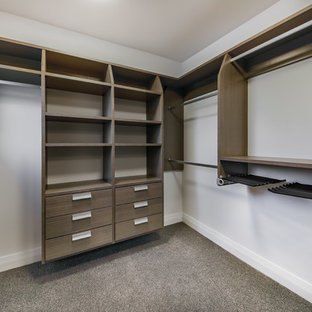Inspiration for a mid-sized beach style gender-neutral walk-in wardrobe in Wellington with open cabinets, dark wood cabinets, carpet and grey floor.