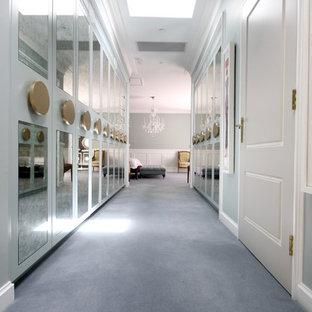 Diseño de vestidor unisex, tradicional, grande, con armarios tipo vitrina, puertas de armario azules, suelo de madera en tonos medios y suelo gris