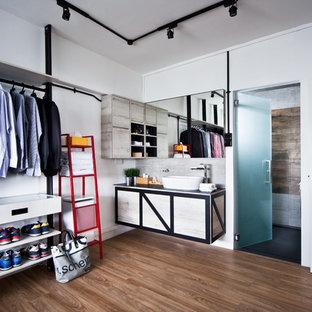 Foto di uno spazio per vestirsi per uomo minimal con ante lisce, ante con finitura invecchiata, pavimento in legno massello medio e pavimento marrone