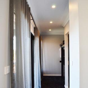 Foto de armario vestidor unisex, minimalista, grande, con puertas de armario de madera en tonos medios, moqueta y suelo azul