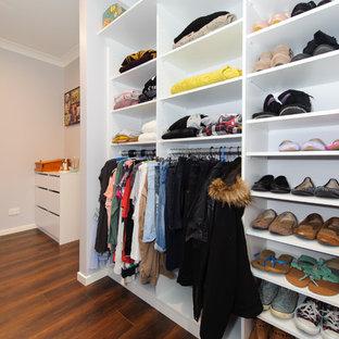 Foto de vestidor unisex, moderno, pequeño, con armarios con paneles lisos, puertas de armario blancas y suelo de madera oscura