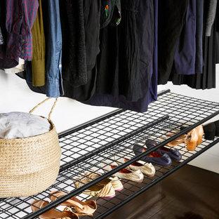 Modelo de armario unisex, minimalista, de tamaño medio, con armarios abiertos, puertas de armario negras, suelo de madera oscura y suelo negro