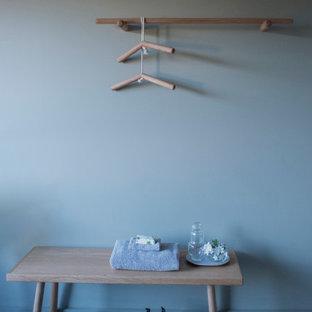 Diseño de armario y vestidor unisex, contemporáneo, pequeño, con armarios abiertos, puertas de armario de madera oscura, suelo de cemento y suelo gris