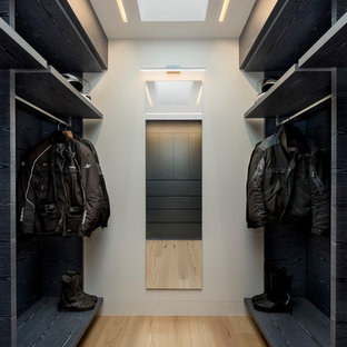 Design ideas for a large contemporary men's dressing room in Sydney with flat-panel cabinets, light hardwood floors, black cabinets and beige floor.