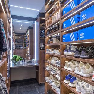 Imagen de armario vestidor unisex, moderno, de tamaño medio, con armarios abiertos, puertas de armario de madera oscura, suelo de baldosas de cerámica y suelo gris