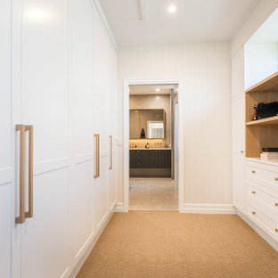 This is an example of a transitional gender-neutral walk-in wardrobe in Brisbane with shaker cabinets, white cabinets, carpet and beige floor.