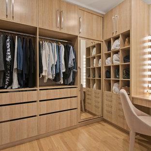 Modelo de armario vestidor unisex, actual, de tamaño medio, con puertas de armario de madera clara, suelo de contrachapado, suelo beige y armarios con paneles lisos
