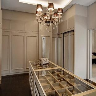 Источник вдохновения для домашнего уюта: гардеробная комната в стиле неоклассика (современная классика) с фасадами с утопленной филенкой, бежевыми фасадами, темным паркетным полом и коричневым полом для женщин