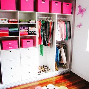 Diseño de armario de mujer, minimalista, de tamaño medio, con armarios con paneles empotrados, puertas de armario blancas, suelo de madera en tonos medios y suelo marrón