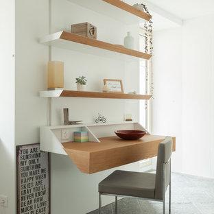 ミラノの中くらいのコンテンポラリースタイルのおしゃれなホームオフィス・書斎 (ライブラリー、白い壁、大理石の床、自立型机、グレーの床) の写真