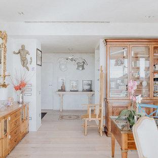 Immagine di uno studio tradizionale con parquet chiaro, libreria, pareti bianche, scrivania autoportante e pavimento beige