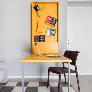 ミラノの小さいコンテンポラリースタイルのおしゃれなアトリエ・スタジオ (グレーの壁、淡色無垢フローリング、自立型机) の写真