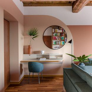 Immagine di uno studio minimal di medie dimensioni con libreria, pareti multicolore, pavimento in legno massello medio, scrivania incassata e pavimento marrone