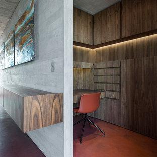 Ispirazione per un piccolo atelier design con pavimento in cemento, scrivania incassata e pavimento rosso