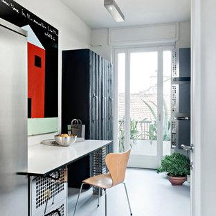 Immagine di un piccolo ufficio design con pareti bianche, pavimento in cemento, nessun camino, pavimento grigio e scrivania incassata
