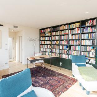 Foto di uno studio minimal con libreria, pareti bianche, parquet chiaro, scrivania autoportante e pavimento beige