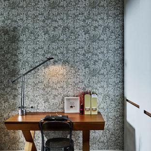 Esempio di un piccolo ufficio minimal con pareti multicolore, pavimento in legno massello medio, scrivania autoportante e pavimento marrone