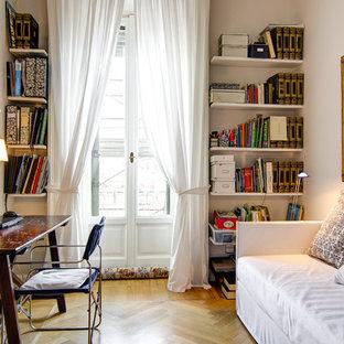 Esempio di uno studio chic di medie dimensioni con libreria, parquet chiaro, scrivania autoportante, pareti beige, nessun camino e pavimento beige