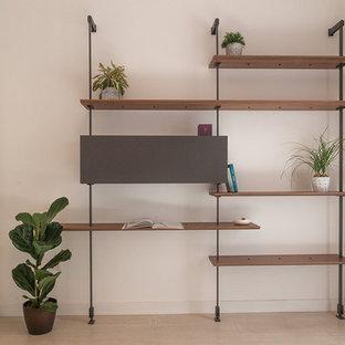 Immagine di un atelier minimal di medie dimensioni con pareti beige, pavimento in laminato e scrivania autoportante