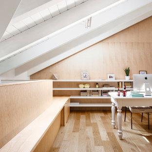 Idee per un grande ufficio minimal con scrivania autoportante, pareti beige e pavimento in legno massello medio