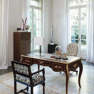 Immagine di uno studio classico con libreria, pareti bianche, scrivania autoportante e pavimento beige
