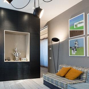 Idee per un'ampia stanza da lavoro eclettica con pareti grigie, parquet scuro, camino bifacciale, cornice del camino in cemento, scrivania autoportante e pavimento grigio