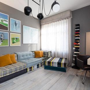 Foto di un'ampia stanza da lavoro bohémian con pareti grigie, parquet scuro, camino bifacciale, cornice del camino in cemento, scrivania autoportante e pavimento grigio