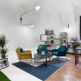 Immagine di un piccolo atelier industriale con pareti bianche, pavimento in terracotta e scrivania autoportante