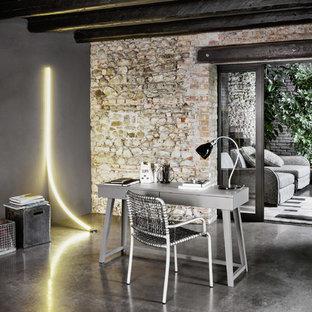 Esempio di un piccolo studio contemporaneo con pareti grigie, pavimento in cemento e scrivania autoportante