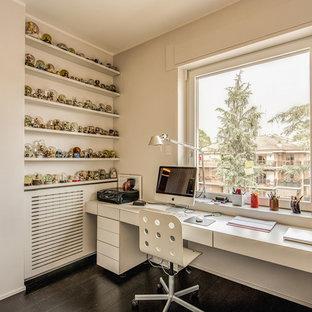 Immagine di uno studio minimal con pareti bianche, parquet scuro, scrivania incassata e pavimento marrone