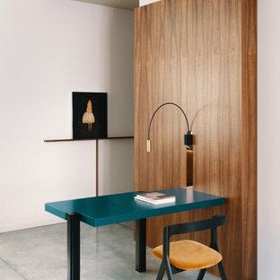 Immagine di un piccolo ufficio design con pareti bianche, scrivania incassata, pavimento grigio e pareti in legno