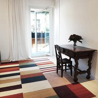 ミラノの広いコンテンポラリースタイルのおしゃれなホームオフィス・書斎 (白い壁、ラミネートの床、グレーの床) の写真