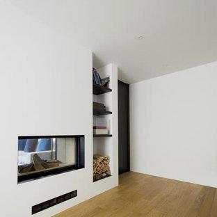 他の地域の広いコンテンポラリースタイルのおしゃれなアトリエ・スタジオ (白い壁、淡色無垢フローリング、両方向型暖炉、漆喰の暖炉まわり、茶色い床) の写真