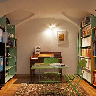 トゥーリンの大きいエクレクティックスタイルのおしゃれなホームオフィス・書斎 (ライブラリー、白い壁、茶色い床、淡色無垢フローリング、造り付け机) の写真