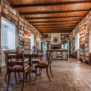 Idéer för ett lantligt arbetsrum, med ett bibliotek, klinkergolv i terrakotta och en dubbelsidig öppen spis
