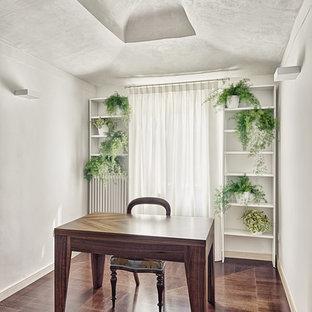 Foto di un atelier moderno di medie dimensioni con pareti bianche, parquet scuro e scrivania autoportante
