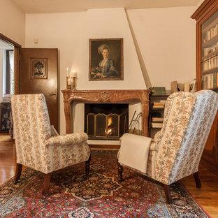 Ispirazione per uno studio classico con camino classico, pareti bianche, pavimento in legno massello medio e pavimento marrone