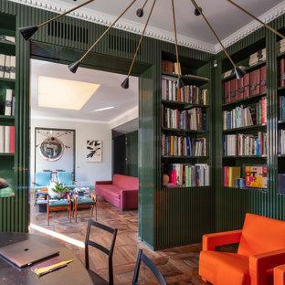 Idee per un grande studio minimal con libreria, pareti verdi, parquet scuro, camino classico, cornice del camino in metallo, scrivania autoportante e pavimento marrone