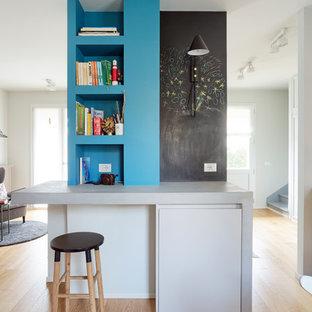Foto di uno studio bohémian con pareti blu, pavimento in legno massello medio, scrivania incassata e pavimento marrone