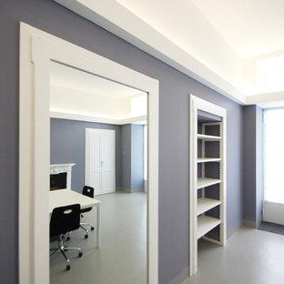 Idee per un atelier design di medie dimensioni con pareti grigie, pavimento in cemento, camino classico, cornice del camino in cemento, scrivania autoportante e pavimento grigio