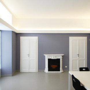 Idee per un atelier contemporaneo di medie dimensioni con pareti grigie, pavimento in cemento, camino classico, cornice del camino in cemento, scrivania autoportante e pavimento grigio