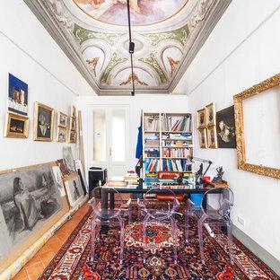 Imagen de sala de manualidades ecléctica, grande, sin chimenea, con paredes blancas, suelo de baldosas de terracota, escritorio independiente y suelo rojo