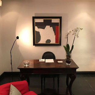 Inspiration for a small midcentury home studio in Rome with beige walls, terracotta flooring, a freestanding desk and black floors.