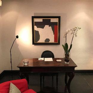 Неиссякаемый источник вдохновения для домашнего уюта: маленькая домашняя мастерская в стиле ретро с бежевыми стенами, полом из терракотовой плитки, отдельно стоящим рабочим столом и черным полом