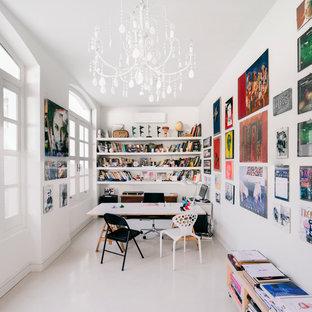 Immagine di uno studio minimal di medie dimensioni con libreria, pareti bianche, scrivania autoportante e pavimento bianco