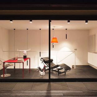 Exempel på ett modernt arbetsrum, med vita väggar, skiffergolv och ett fristående skrivbord